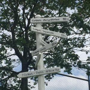Wegweiser am Sportplatz in Eschbach/Pfalz. 183 Kilometer sind es bis in unser Eschbach an der Loreley.